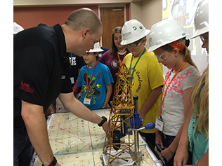 Man teaching kids about oil rigs